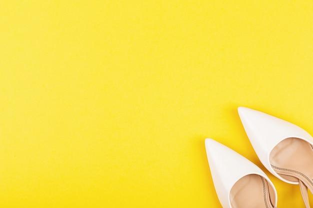 Weiße weibliche modeschuhe auf gelbem hintergrund