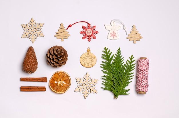 Weiße weihnachts- oder neujahrsoberfläche mit wacholderzweig, zimt, anis, geschenkbox, trockenen orangen, holzspielzeug, karamell-weihnachtssüßigkeiten, tannenzapfen, nüssen