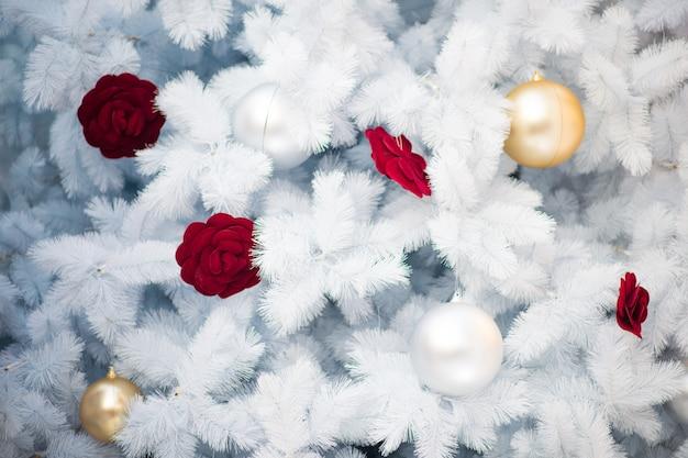 Weiße weihnachtsdekoration mit roten bällen und silbernen bällen auf weihnachtsbaum