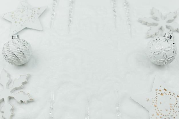 Weiße weihnachtsdekoration und zweige der tanne auf schnee, weißer weihnachtshintergrund, weiße weihnachtskugeln.