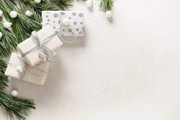 Weiße weihnachtsgeschenke und immergrüne zweige auf weißem hintergrund. weihnachtskarte für ärzte.