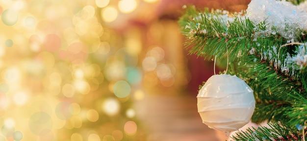 Weiße weihnachtskugel, die auf einem schneebedeckten tannenbaumzweig, bokeh-effekthintergrund hängt