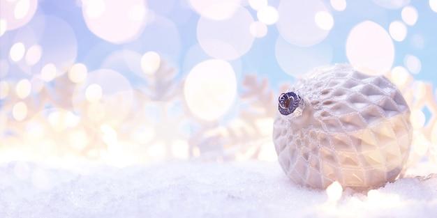 Weiße weihnachtskugel mit schneeflocken auf blau