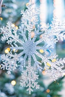 Weiße weihnachtsschneeflocke, die vom baum hängt