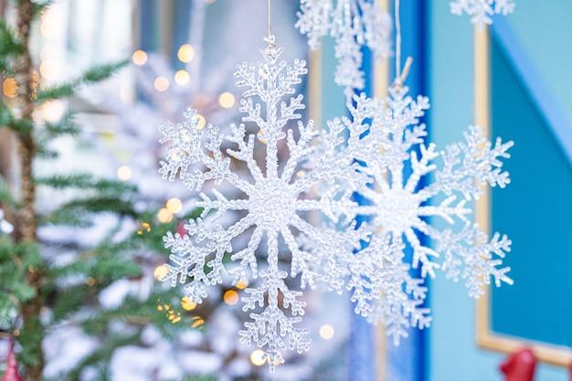 Weiße weihnachtsschneeflocken, die vom baum hängen