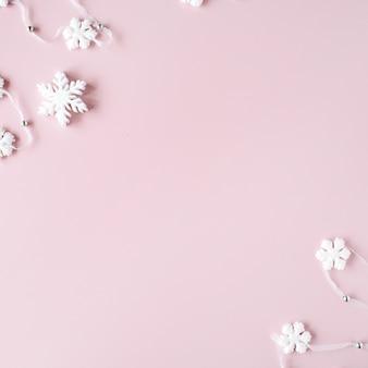 Weiße weihnachtsschneeflockendekoration auf rosa hintergrund. weihnachtstapete. Premium Fotos