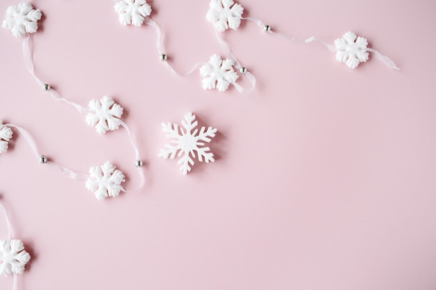 Weiße weihnachtsschneeflockendekoration auf rosa hintergrund. weihnachtstapete.