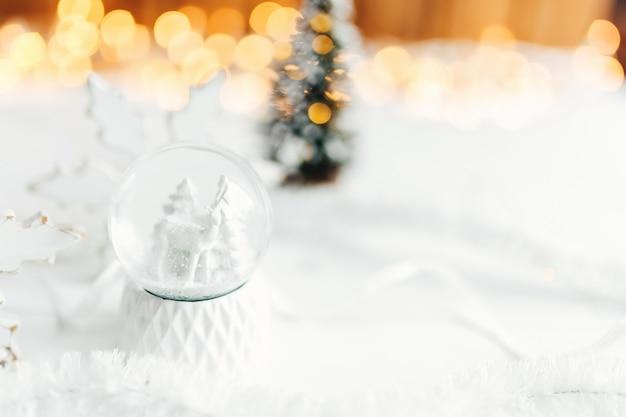 Weiße weihnachtsschneekugel auf einem tisch mit weihnachtsdekorationen. foto in hoher qualität