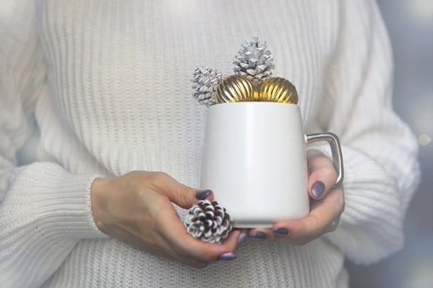 Weiße weihnachtstasse auf frauenhänden mit tannenzapfenwinterbecher hautnah für neujahrszeitkonzept
