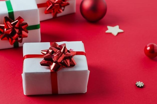 Weiße weiße handgemachte geschenkboxen auf einem roten hintergrund gebunden mit einem roten band. fröhliche weihnachten