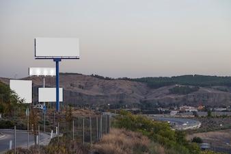Weiße Werbetafeln auf der Autobahn mit Bergen im Hintergrund