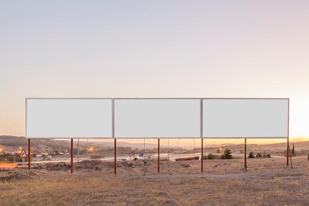 Weiße werbetafeln für werbung nahe der landstraße während des sonnenuntergangs
