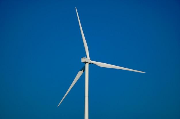 Weiße windkraftanlage mitten auf der wiese