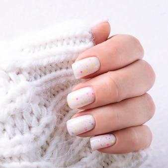 Weiße wintermaniküre mit süßigkeiten. handnahaufnahme.