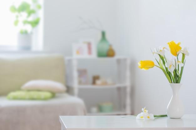 Weiße wohneinrichtung mit frühlingsblumen und dekorationen