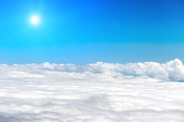 Weiße wolken am blauen himmel mit strahlender sonne als naturhintergrund