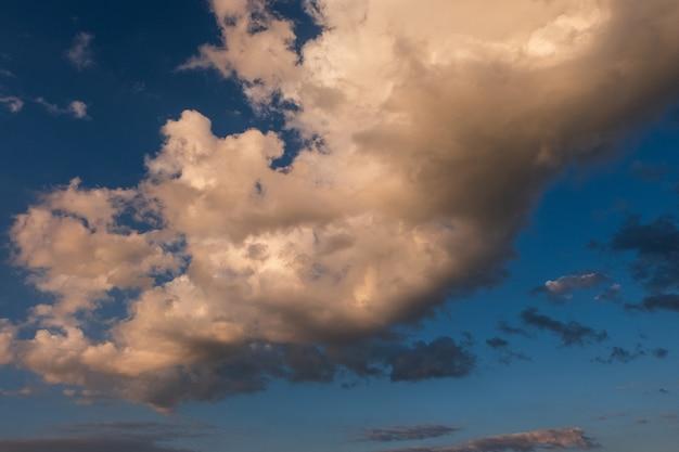 Weiße wolken im blauen himmel des sommers an der goldenen stunde