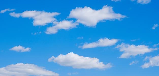 Weiße wolken in einem freien idyllischen blauen himmel an einem sonnigen sommertag.