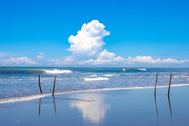 Weiße wolken über dem blauen meer mit himmelsreflexion am strand