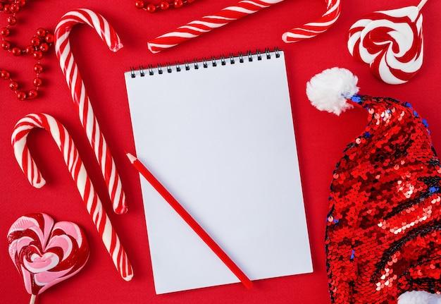 Weiße wunschliste leer mit bonbons und weihnachtsmütze auf rotem hintergrund