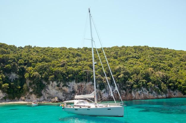 Weiße yacht, die an einem sonnigen tag in der türkisfarbenen lagune segelt