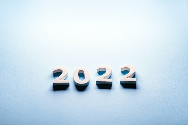 Weiße zahlen 2022 auf blauem hintergrund minimalismus-postkarte 2022ausgeschnittene zahlen 2022fröhlich