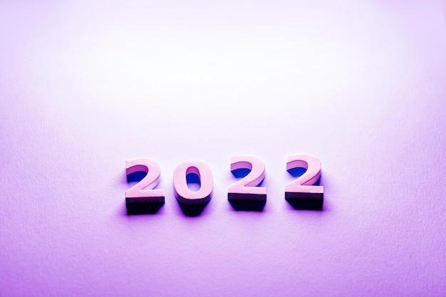 Weiße zahlen 2022 auf rosa hintergrund minimalismus-postkarte 2022 scherenschnitt-zahlen 2022
