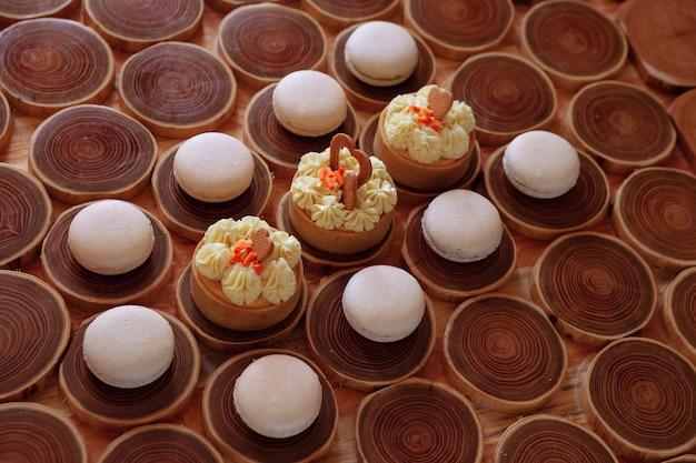 Weiße zarte niedrige makronen auf einem hölzernen hintergrund der pastellton der creme innerhalb der französischen kekse
