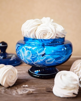 Weiße zephyr-marshmallows des süßen nachtischs in der blauen glasvase auf dem holztisch