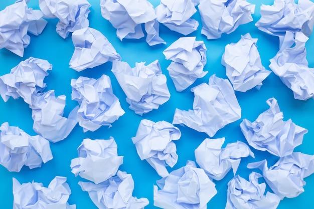 Weiße zerknitterte papierkugeln auf einem blauen hintergrund.