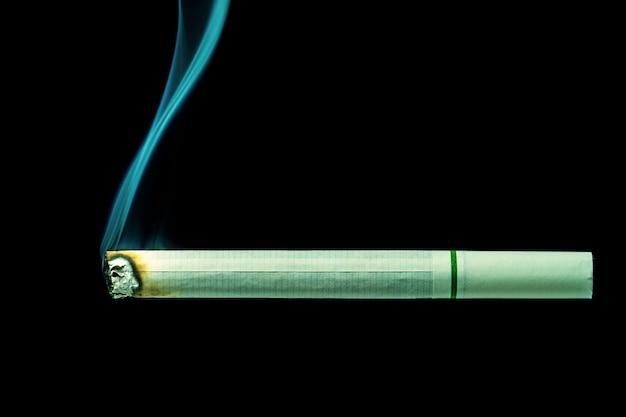 Weiße zigarette brennt auf schwarzem hintergrund