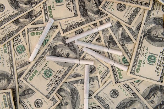 Weiße zigaretten, die auf den dollarnoten liegen. konzept der finanziellen kosten des rauchens.
