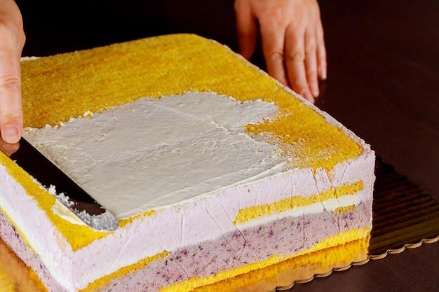 Weiße zuckergusscreme auf die kuchenschicht geben