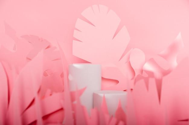 Weiße zylinderpodeste unter tropischen papierblättern. vitrinenpodeste für kosmetische produkte.mock-up für die ausstellungen,präsentation von produkten,