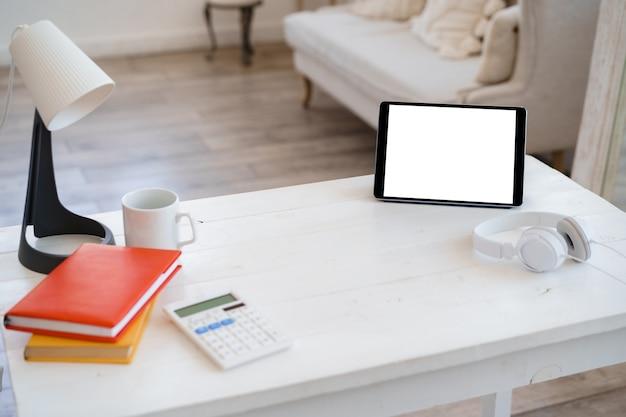 Weißer arbeitstisch mit digitaler tablette des leeren bildschirms