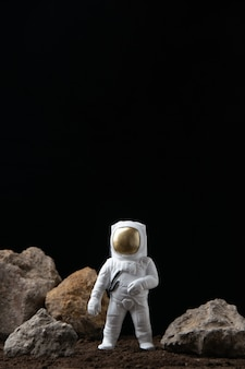 Weißer astronaut auf mond mit felsen auf einer dunklen science-fiction-fantasie