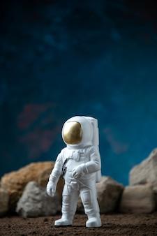 Weißer astronaut um felsen auf einem mondblauen fantasy-kosmischen science-fiction-film