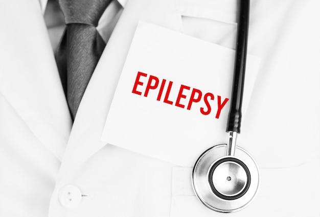 Weißer aufkleber mit text epilepsie, die auf medizinischem gewand mit einem stethoskop liegt