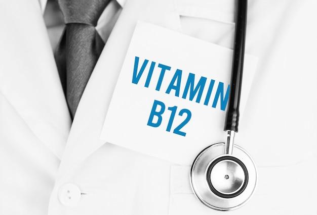 Weißer aufkleber mit text vitamin b12, der auf medizinischem gewand mit einem stethoskop liegt