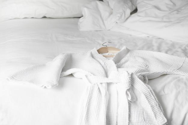 Weißer bademantel auf dem bett im hotelzimmer