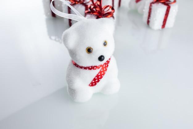 Weißer bär des weihnachtsbaumspielzeugs nahe weihnachtsgeschenkboxen mit band