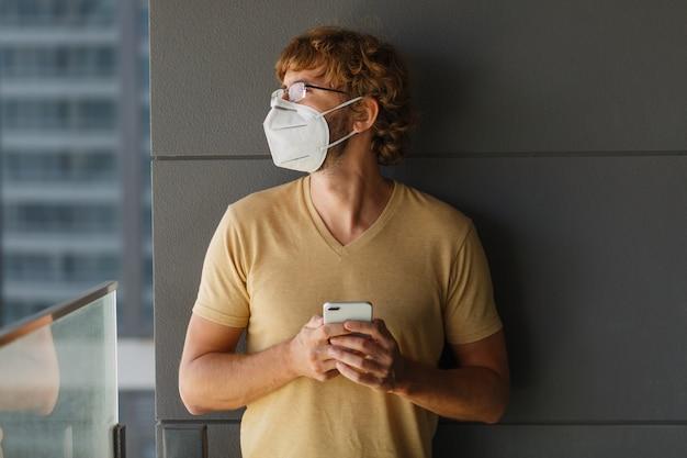 Weißer bärtiger erwachsener mann, der smartphone beim tragen der chirurgischen maske auf einer industriellen wand verwendet. gesundheit, epidemien, soziale medien.