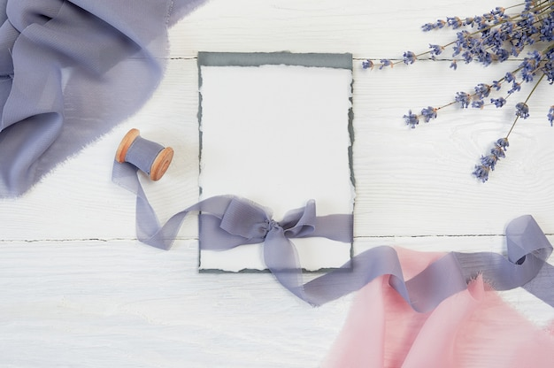 Weißer bandbogen der leeren karte mit den rosa und blauen gewebe- und lavendelblumen