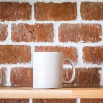 Weißer becher auf weinlesebacksteinmauerhintergrund