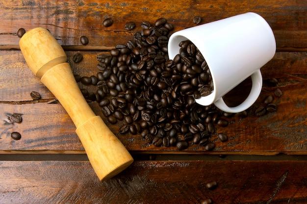 Weißer becher mit den gebratenen und frischen kaffeebohnen gegossen über rustikalem holztisch. draufsicht