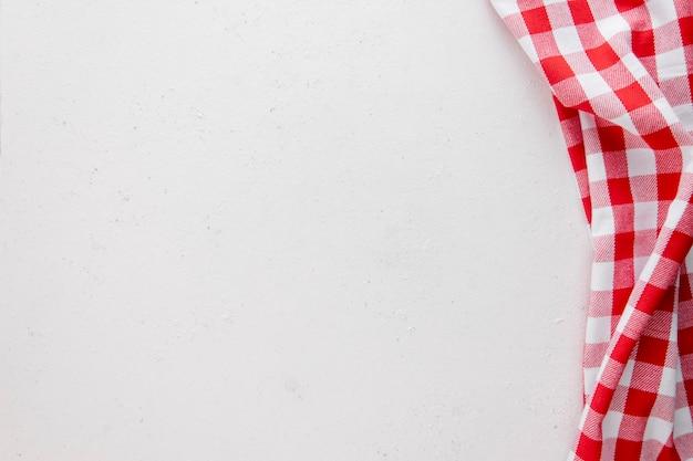 Weißer betonhintergrund mit roter und weißer serviette. platz kopieren