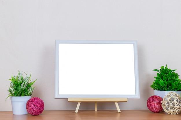 Weißer bilderrahmen auf hölzerner tabelle.