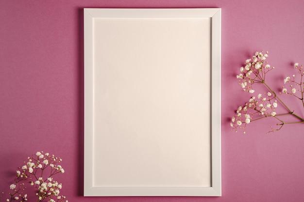 Weißer bilderrahmen mit leerer schablone, gypsophila-blumen, rosa lila pastellhintergrund, modellkarte