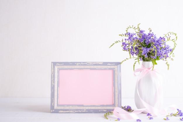 Weißer bilderrahmen mit reizender purpurroter blume im vase auf weißem holztisch