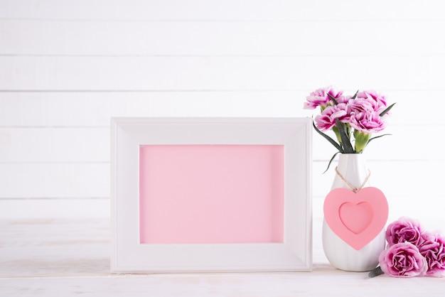 Weißer bilderrahmen mit rosa gartennelkenblume im vase auf weißem holztisch.